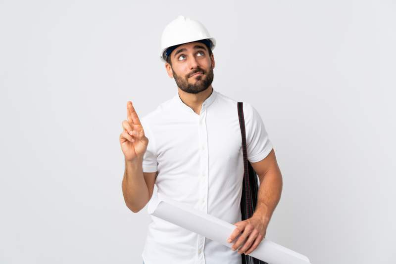 Young architect man with helmet and holding blueprints isolated on white wall with fingers crossing and wishing the best